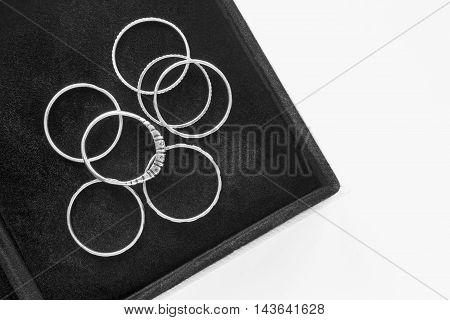 Group of silver rings in black jewel box closeup