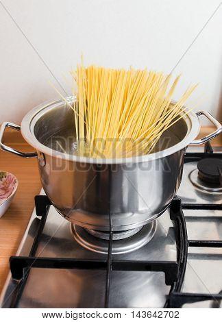 Spaghetti in pan cooking in boiling water.