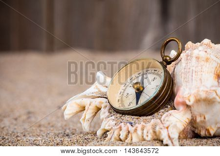 Vintage compass with shell on sand with wooden fence background