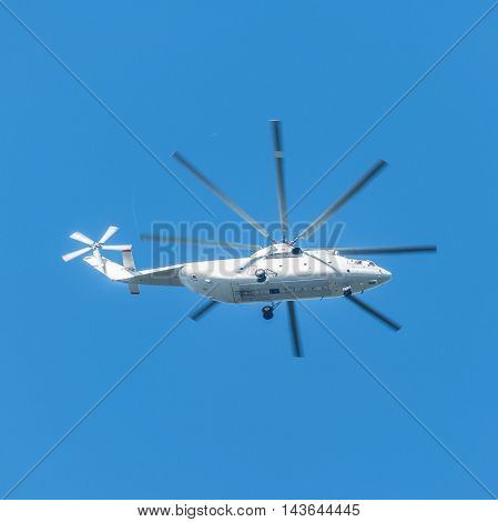 White transport helicopter flyong in the blue sky.