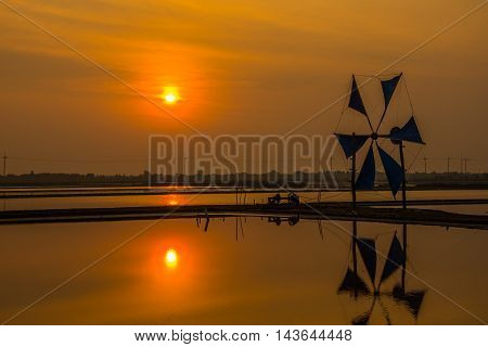 Salt farm with windmill to feed sea water to the farm in early morning