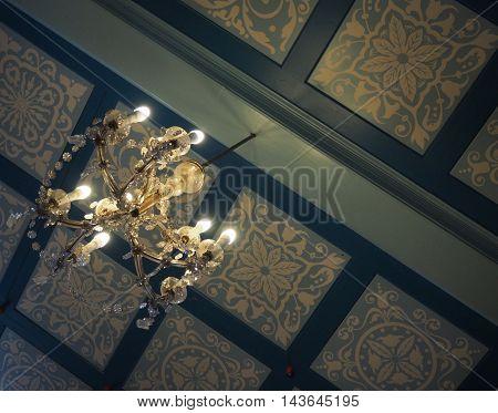 Rento Vintage Chandelier Against Blue Pattern Ceiling