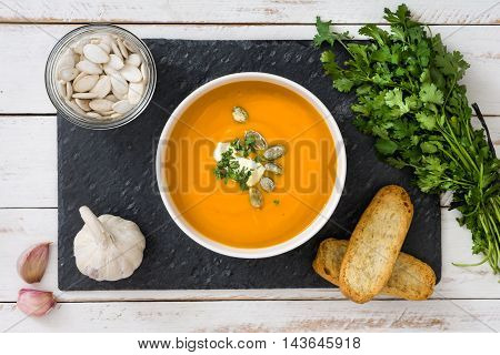 Pumpkin soup on slate plate and a white wooden table