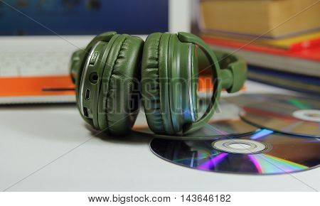 big green earphones on a desktop with disks and the computer