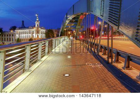 Iron arched Mindaugas Bridge across Neris River in Vilnius with night lighting. Lithuania.