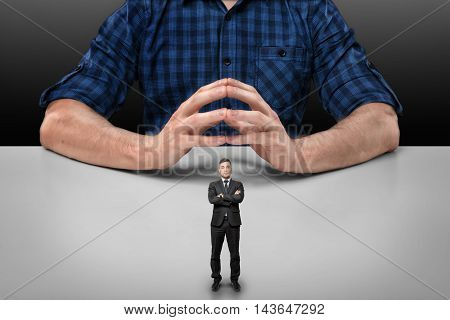 Businessman with folded arms stands in front of a cropped portrait of a big man sitting with his fingers clasped. Business staff. Boss and employee. Big and small business. Community and teamwork.