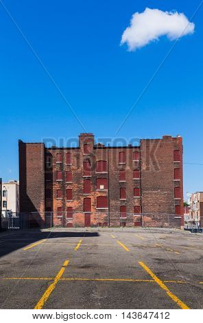 Yellow lines of an empty parking place and an abandoned building made of bricks. Bright blue sky with one single white cloud. Detroit Michigan USA.