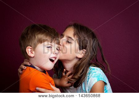 An older sister kisses her little brother on the cheek as he pushes her away with a disgusted look on his face.