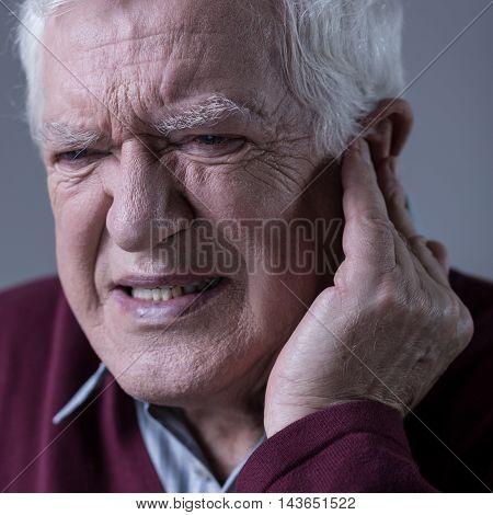 Senior elegant man with terrible sharp earache