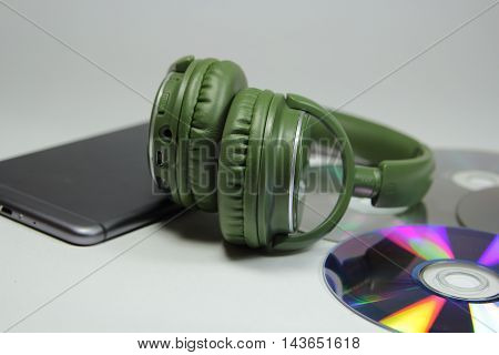 big green earphones on a desktop and phone with disks