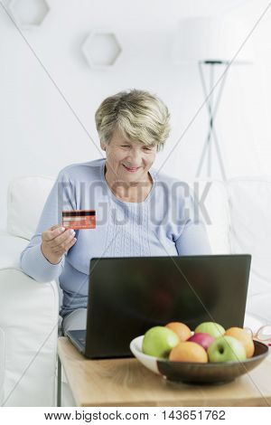 Shot of a smiling senior woman holding a credit card and looking at a laptop