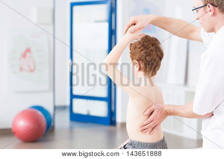 Physiotherapist during exercises with boy light interior