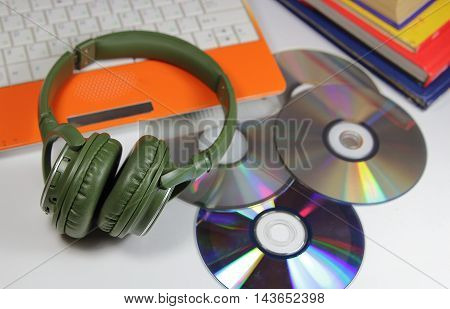 big green earphones on a desktop and the computer with disks