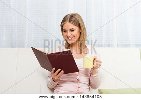 Young beautiful woman is reading a book,drinking tea or coffee and enjoys in her free time at home.