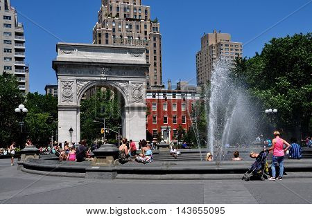 New York NY - June 1 2013: Washington Square Park with its fountain and Triumphal Arch commemorating George Washington with Fifth Avenue luxury apartment towers
