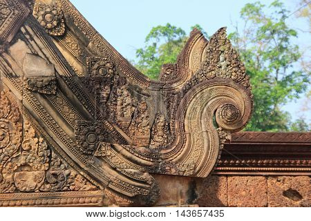 Red sandstone carvings on a temple called Banteay Srei located Cambodia