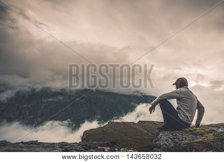Resting with Scenic View. Hiker Resting on the Rock and Watching Scenic Cloudy Landscape.