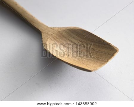 close up of the wooden spoon on the white background