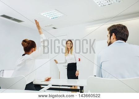 Businesswoman at the meeting raised a hand