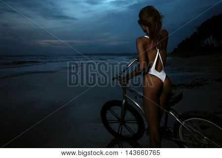 Young woman in bikini standing on the shore with her bike and enjoying the sunset over the sea