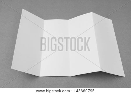 Four - fold white template paper on gray  background