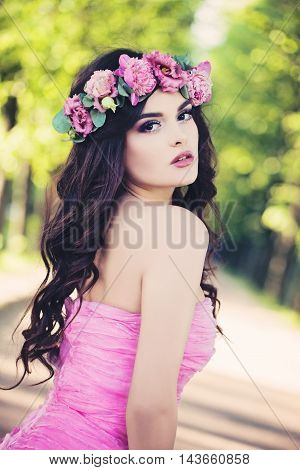 Outdoors Portrait of Fashion Woman. Beauty Summer Girl with Flowers on Sunny Greenery Background