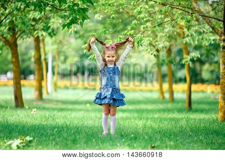 Cheerful and happy little girl with arms outstretched summer in blue dress outdoors in a park smiles sweetly.