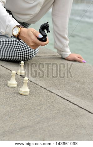 Woman Holds Chess Knight In Her Hand.