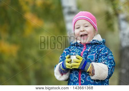 Seasonal outdoor head and shoulders portrait of little girl is holding steel thermos flask cup in hands