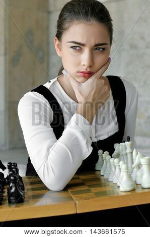 Girl Put Her Hand To Her Cheek Before The A Chess Game.