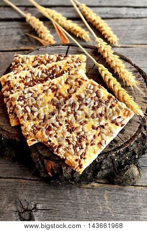 Wholesome cookies with sunflower seeds, flax seeds and sesame seeds. Vegetarian cookies snack. Ears of wheat on old wooden background
