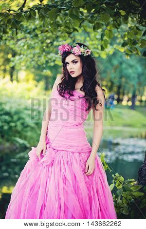 Fashion Girl Outdoors Portrait in Greenery Blooming Trees. Beauty Romantic Woman with Flowers. Beautiful Woman Enjoying Nature