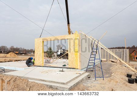 Roofer builder workers with crane installing structural Insulated Panels SIP. Building new frame energy-efficient house