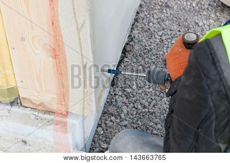 Worker use drill to make a hole in structural Insulated Panel