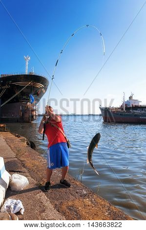 Naples Italy - August 10 2016: Boy fishing mullet with the barrel on the platform of the industrial port. In the background a ship repair firm in the pipeline.