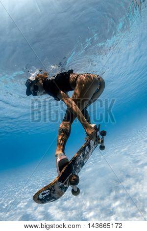Woman skateboarding underwater in the swimming pool