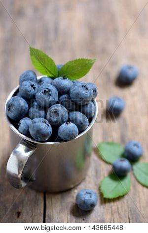 Blueberries in mug on a wooden background