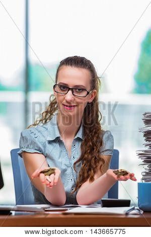 Young businesswoman with coins in the office
