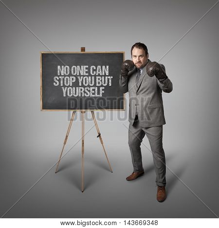 No one can stop you but yourself text on  blackboard with businessman wearing boxing gloves