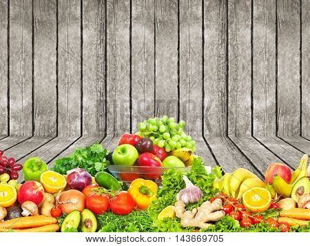 Vegetables and fruits over wooden wall background.