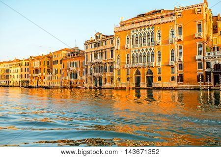 Beautiful waterfront with colorful gothic buildings and boats on Gran canal at the sunrise