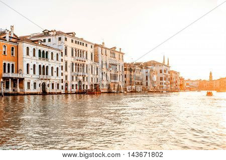 Beautiful waterfront with gothic buildings and boats on Gran canal at the sunrise