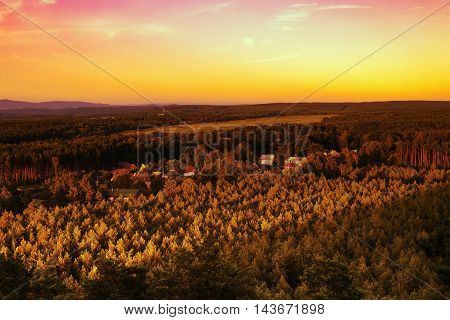 Sunset over the village Hradcany with airports in the background among the pine forests in the tourist area Machuv kraj in czech landscape