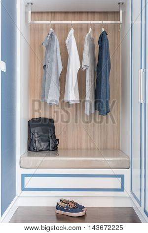 Clothes Hang On Rail In Wooden Closet With Black Bag