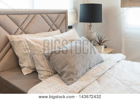 Single Bed In Modern Bedroom With Black Lamp And Vase Of Plants