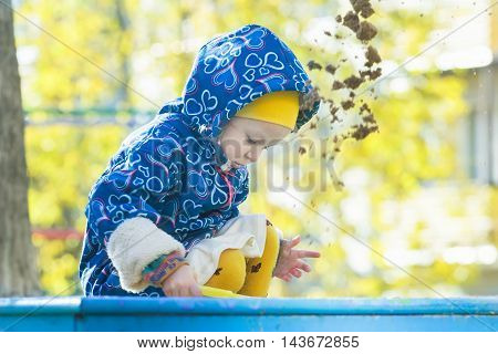 Little girl is playing in sandbox outdoors at autumn yellow shrubbery and trees leaves background