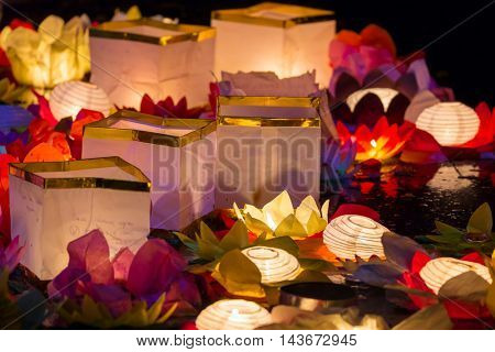 Floating paper lanterns on the water at night