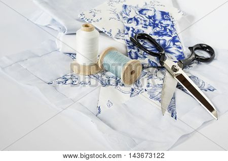 Threads, fabrics and other sewing accessories on white