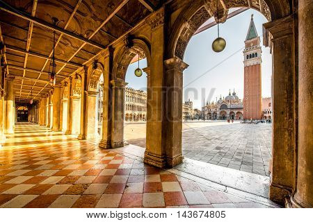 Arches of Correr museum with San Marco tower on the main square in the morning in Venice