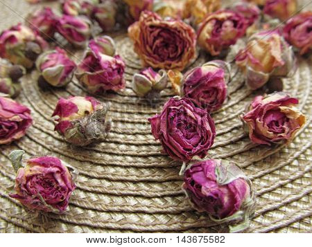 Closeup of dried roses buds on wicker rug background